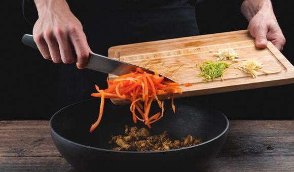 Добавление овощей и цедры в сковороду с обжаренными кусочками курицы