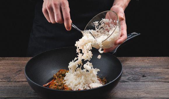 Перекладывание отварного риса в сковороду с заготовкой для риса по-тайски