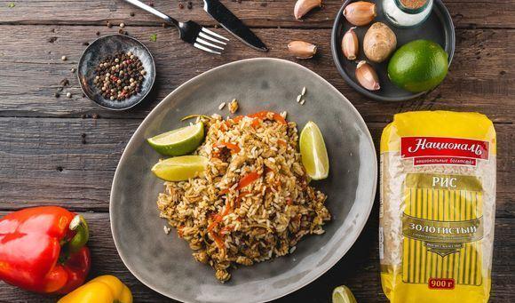 Жареный рис по-тайски в большом блюде на сервированном столе