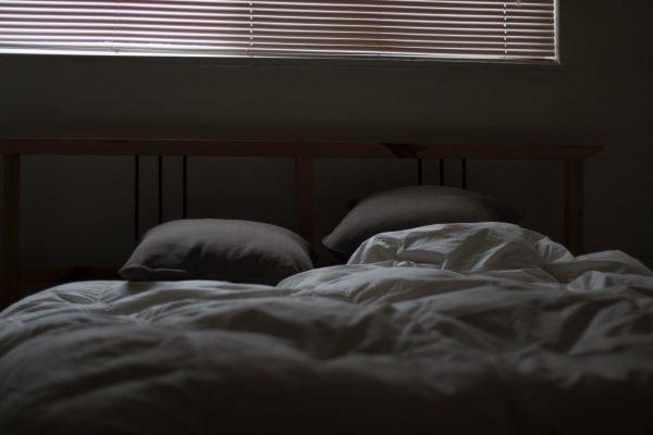 Серая незаправленная кровать