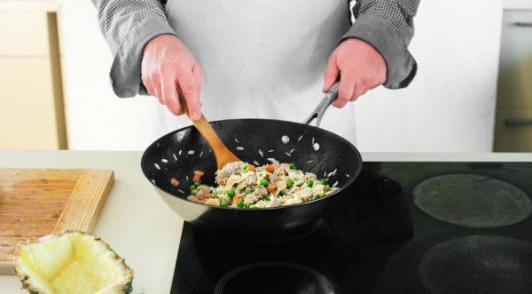 Приготовление риса по-тайски в большой сковороде на электрической плите
