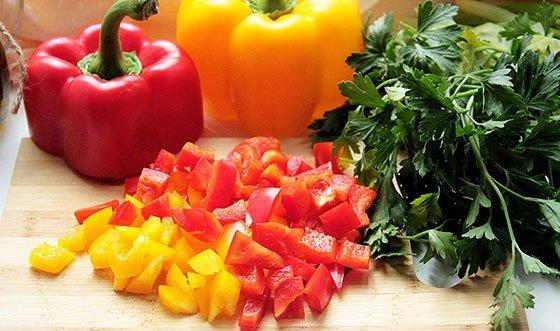 Разноцветный болгарский перец и свежая петрушка на разделочной доске