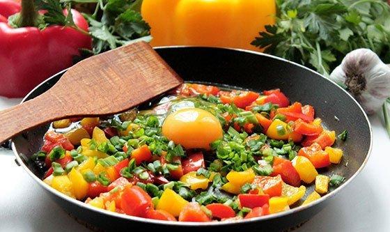 Кусочки болгарского перца, зелёный лук и сырое яйцо в сковороде с деревянной лопаточкой