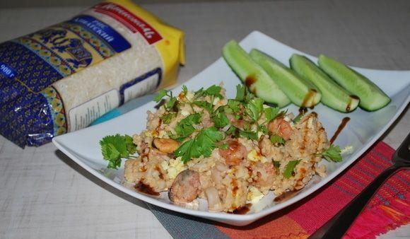 Рис по-тайски с морепродуктами и свежей кинзой на прямоугольной белой тарелке