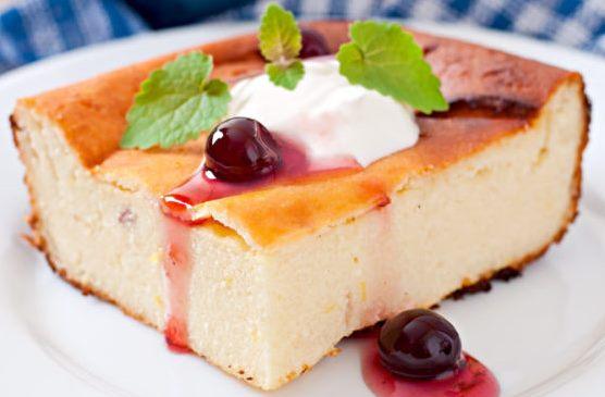Кусочек творожной запеканки с вареньем, натуральным йогуртом и листьями мяты на тарелке