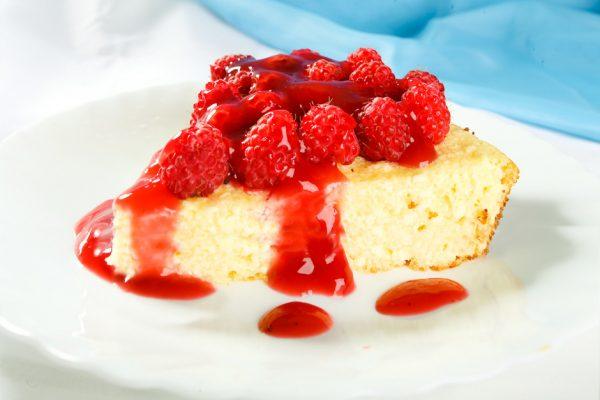 порционный кусочек творожной запеканки с малиной и ягодным соусом на белой тарелке