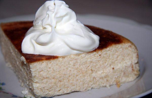 Кусочек творожной запеканки с натуральным йогуртом на тарелке