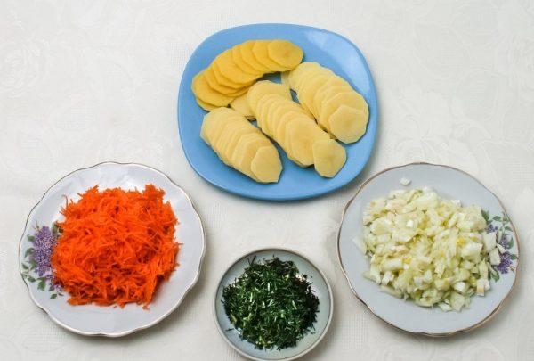Подготовленные овощи и зелень в разных тарелках на столе