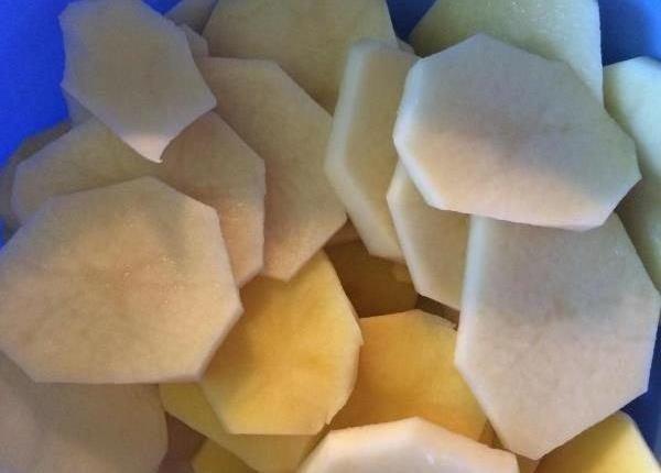 Нарезанный тонкими пластинами сырой картофель