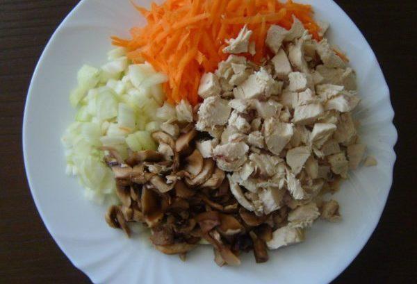 Измельчённый репчатый лук, тёртая морковь, кусочки шампиньонов и нарезанная кубиками отварная куриная грудка на белой тарелке
