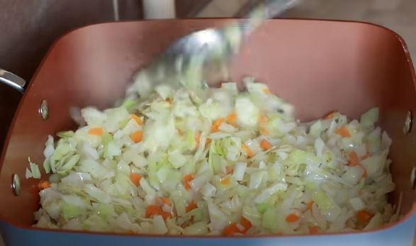 Измельчённая белокочанная капуста с морковью и луком в сковороде