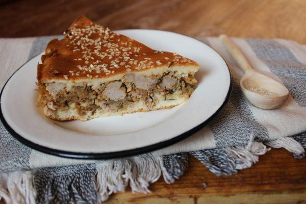 Порционный кусочек заливного пирога с капустой и мясным фаршем на столе с деревянной ложкой