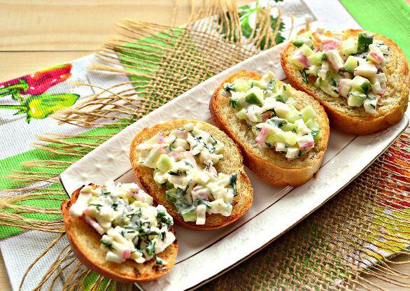 Бутерброды с плавленым сыром, крабовыми палочками и свежим огурцом на красивой салфетке