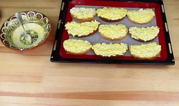 Заготовки для горячих бутербродов на противне и пустая миска из-под сырной массы
