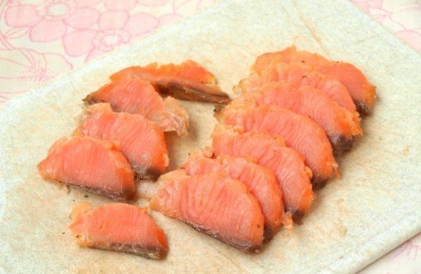 Ломтики красной рыбы на разделочной доске