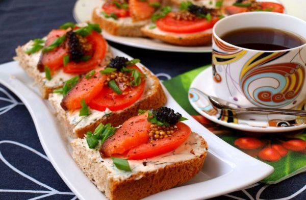 Бутерброды с красной рыбой, плавленым сыром и помидором на сервированном столе