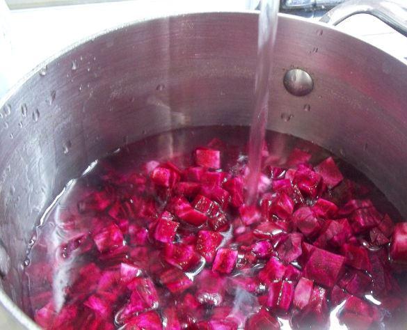измельчённая свёкла в большой кастрюле с водой и открытый кран