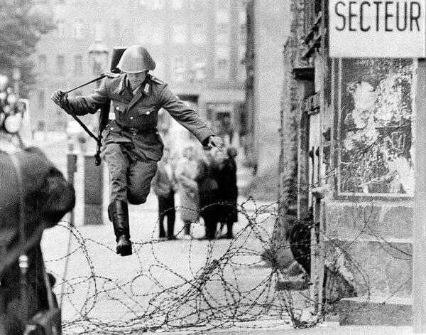 Солдат перепрыгивает через колючую проволоку