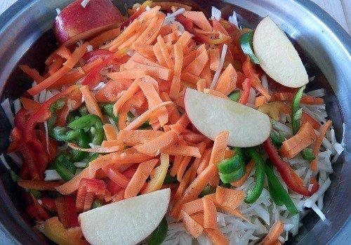Нашинкованные овощи и кусочки яблока в металлической миске
