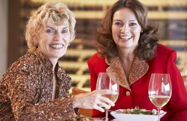 Пожилые женщины в кафе улыбаются и пьют вино