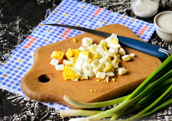 Нарезанные кубиками отварные яйца на деревянной разделочной доске с ножом