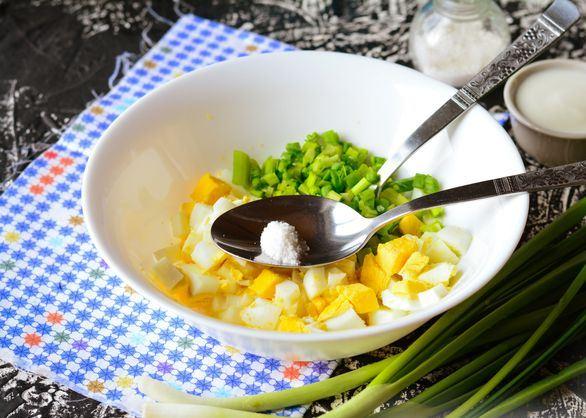 Ложка с солью в глубокой тарелке с отварными яйцами и зелёным луком