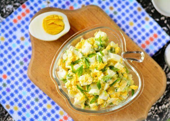 Луково-яичный салат к красивом порционном салатнике на деревянной разделочной доске