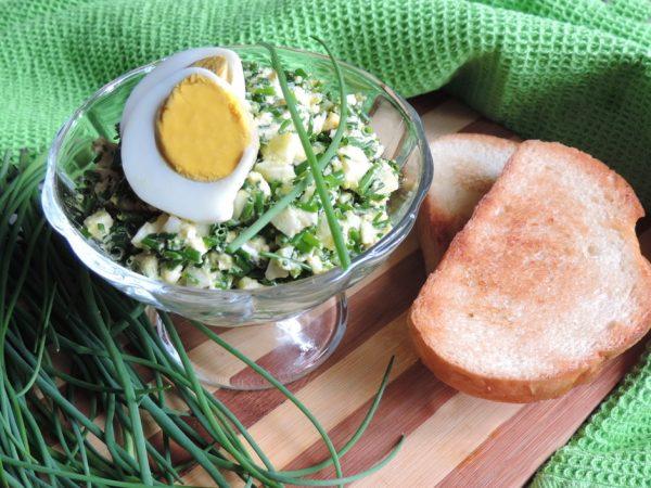 луково-яичный салат с плавленым сыром на разделочной доске с гренками и зеленью
