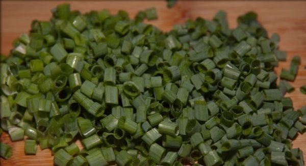 Мелко нарезанные перья зелёного лука на деревянной поверхности