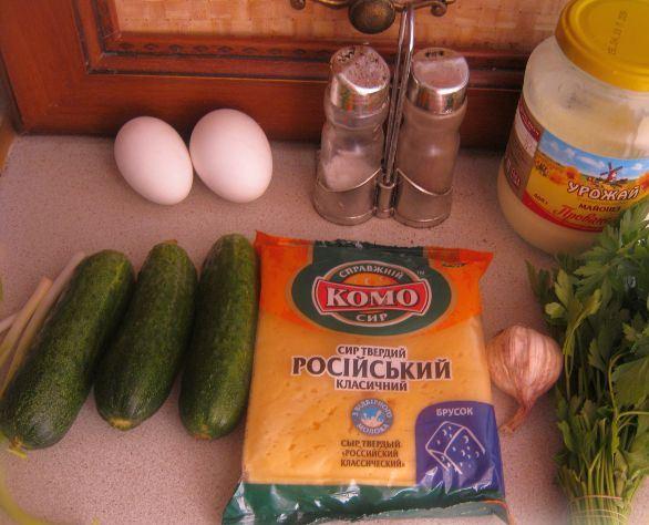 Продукты для приготовления салата из яиц, сыра, зелёного лука и огурцов на столе