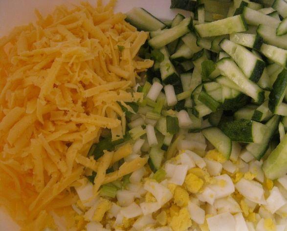 Рубленый отварные яйца. нарезанные соломкой огурцы и тёртый твёрдый сыр в миске