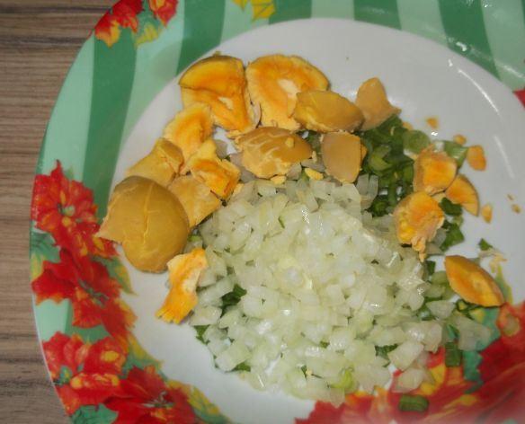 Варёные яичные белки, мелко нарезанный лук в тарелке