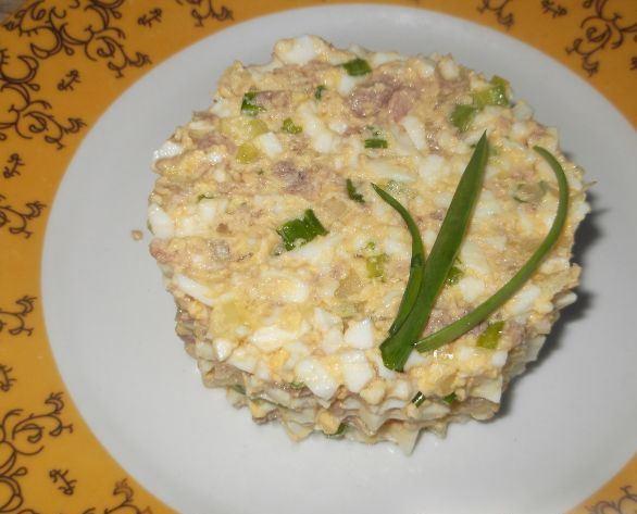 Порция салата из яяиц, зелёного лука и печени трески, украшенная зелёным луком