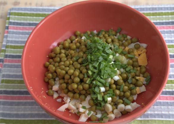 Измельчённые отварные яйца. рубленый зелёный лук и консервированный горошек в красной миске