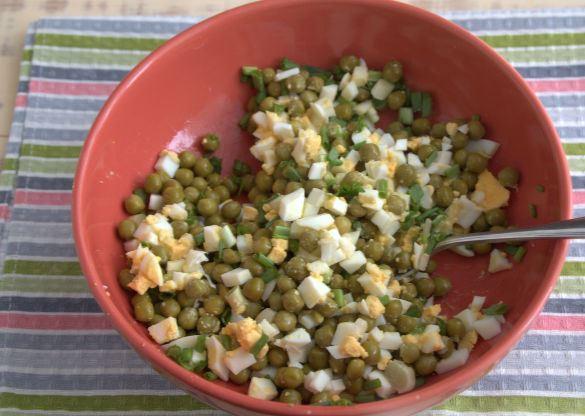 Перемешанные ингредиенты салата из яиц, зелёного лука и консервированного горошка в красной миске