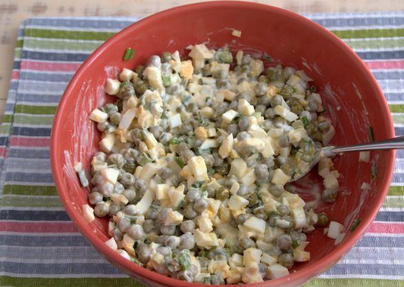 Салат из яиц, зелёного лука и консервированного горошка в красной миске