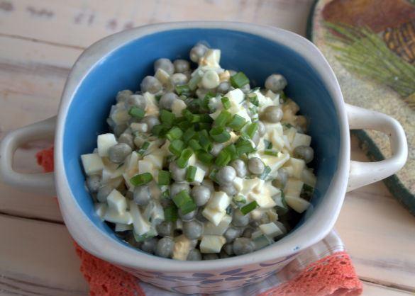 Салат из яиц, зелёного лука и консервированного горошка с зеленью в красивом салатнике на салфетке