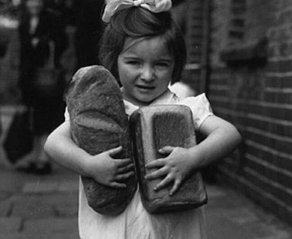 Девочка несёт в руках буханку хлеба и батон