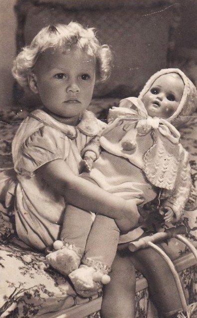 Девочка аккуратно держит куклу