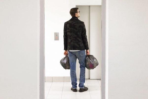 Мужчина стоит у лифта с мусором