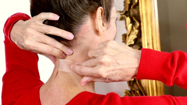 Девушка наклеивает скотч на шею
