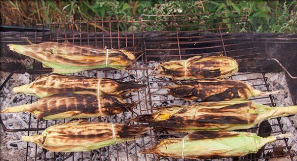 Запечённые кукурузные початки с листьями на решётке мангала