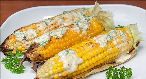 Приготовленная на мангале кукуруза в листьях со сливочным соусом на тарелке