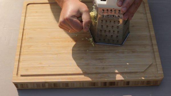 Измельчение кусочка имбирного корня с помощью металлической тёрки