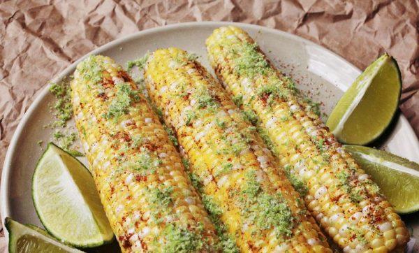 Кукурузные початки с со специями, цедрой и дольками лайма на большой белой тарелке