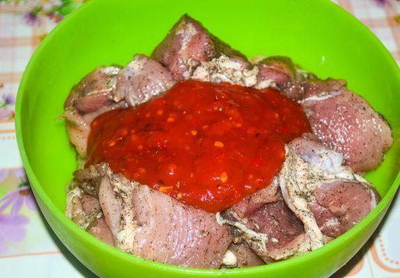 Кусочки сырого свиного мяса со специями и томатным соусом в зелёной пластмассовой миске