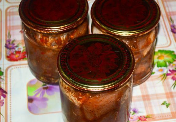 Закрытые металлическим крышками банки со свиной тушёнкой в томатном соусе