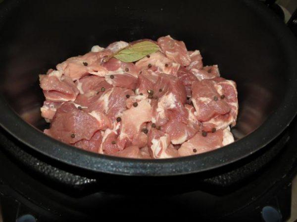 Нарезанная кусочкам и сырая свинина со специями в чаше мультиварки