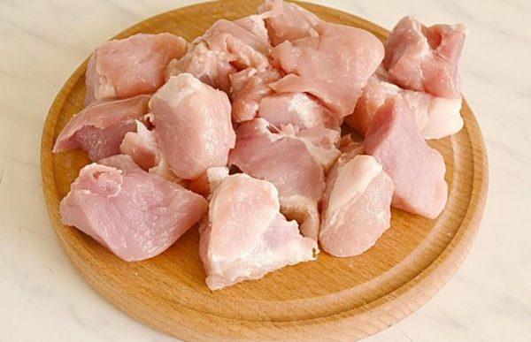 Кусочки сырой свинины на круглой разделочной доске из дерева