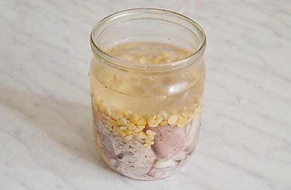 Кусочки сырой свинины, сухой горох и вода в стеклянной банке